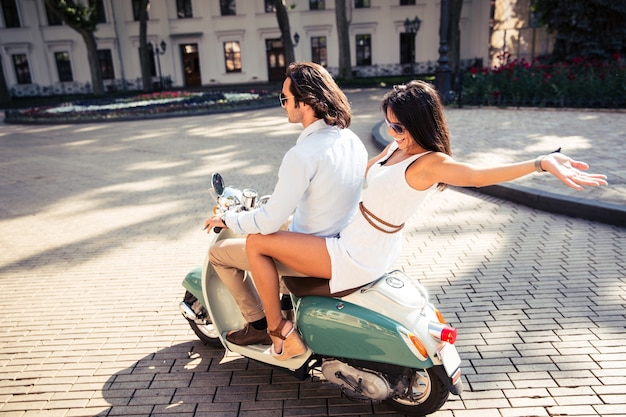 Happy couple riding a scooter