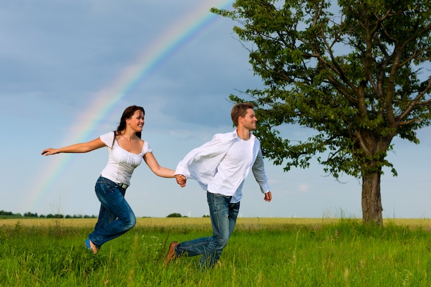 Happy couple running on a meadow