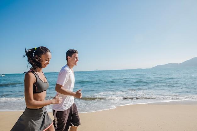 ビーチで走っている幸せなカップル