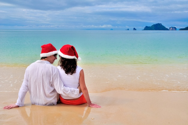 Happy couple in santa hats relaxing on tropical sandy beach near sea, christmas and new year holiday romantic vacation
