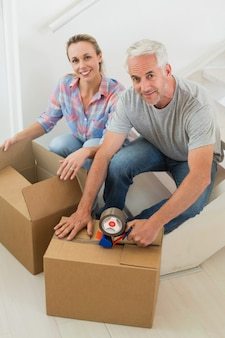 Happy couple sealing cardboard moving boxes