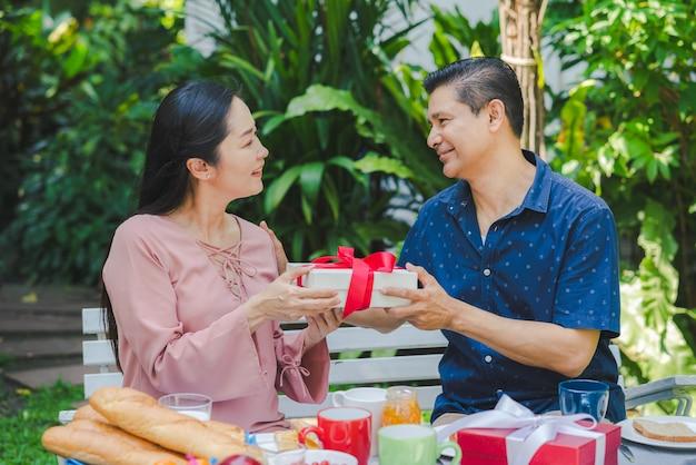 幸せなカップルの年配の男性が自宅の庭で朝食をとりながら彼の妻にギフトボックスを与える