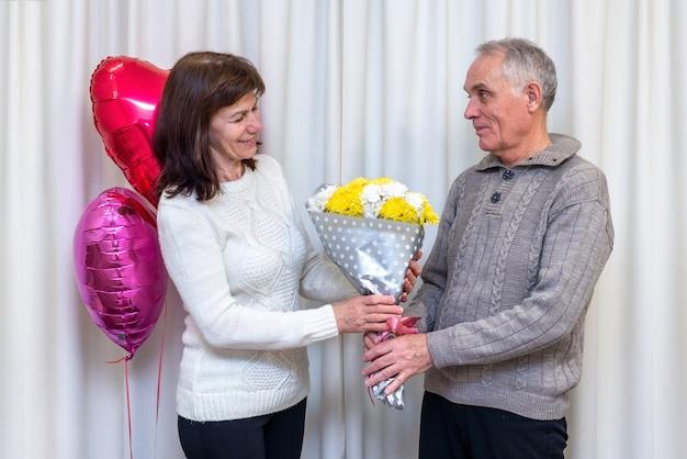 Счастливая пара пожилых людей празднует день святого валентина. мужчина дарит женщине любимый букет цветов