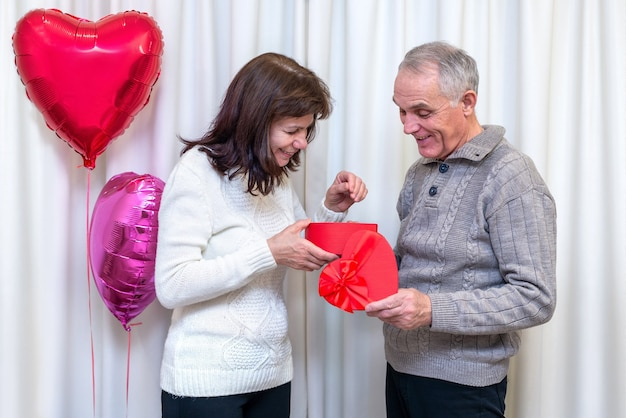 Happy couple seniors celebrate valentine's day. man gives a woman gift box in shape of a heart