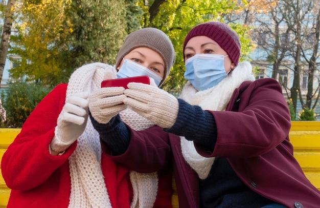 Счастливая пара пожилых людей или женщины среднего возраста носят защитную медицинскую маску и сидят на скамейке в осеннем парке.
