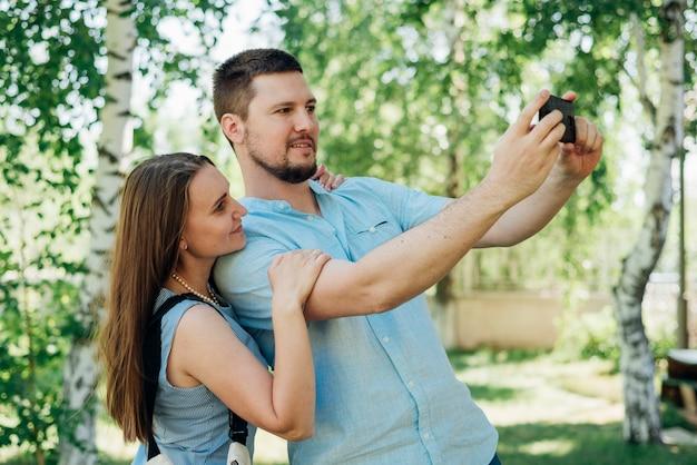 Happy couple shooting selfie in park