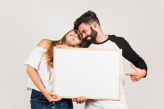 Happy couple showing blank board