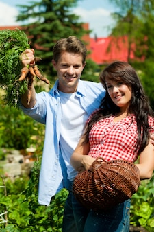 Happy couple showing off the vegetables they are harvesting