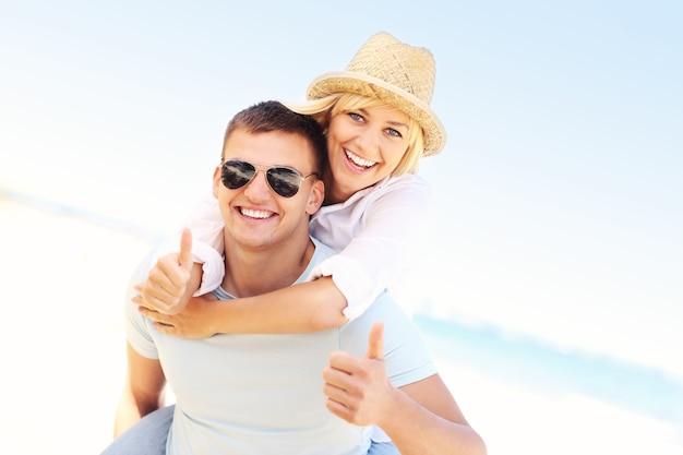 Счастливая пара показывает знак ок на пляже