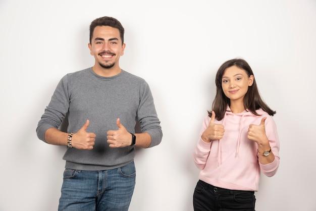 白で親指を示す幸せなカップル。