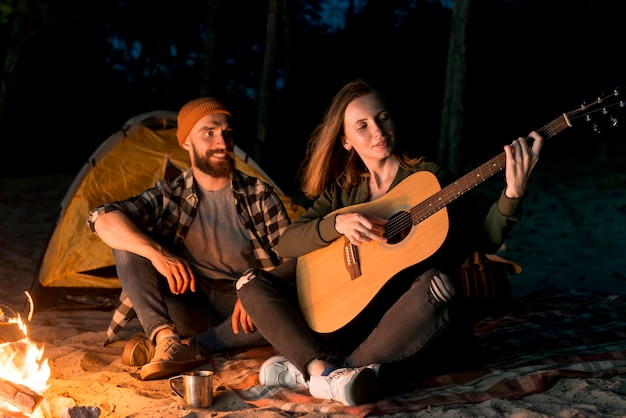 Happy couple singing and playing the guitar