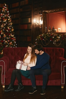 Happy couple sits on the red couch, handsome man embracing model woman which keeps christmas gift box