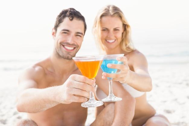 幸せなカップルに座って、カクテルを飲む