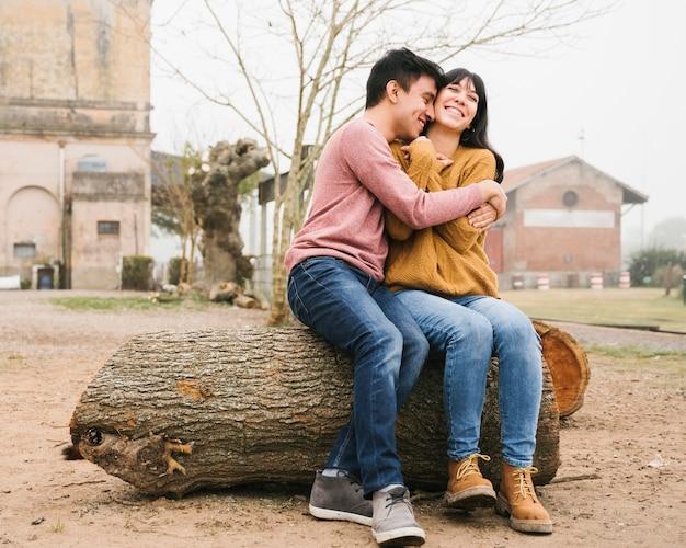 Счастливая пара сидит и обниматься на бревно