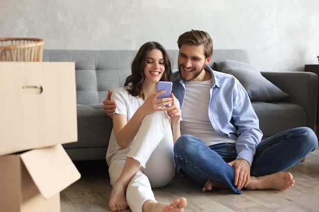 幸せなカップルが座って、引っ越しの日にスマートフォンで家の新しい家の装飾を計画し、新しい家のリフォームとインテリアデザイン。