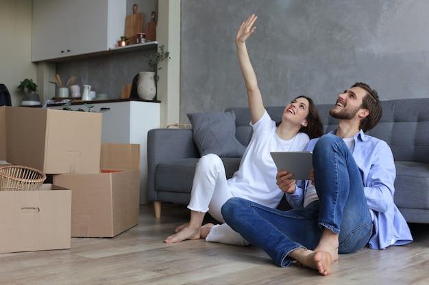 幸せなカップルが座って、引っ越しの日にタブレットを使って家で新しい家の装飾を計画し、新しい家のリフォームとインテリアデザインを計画しています。