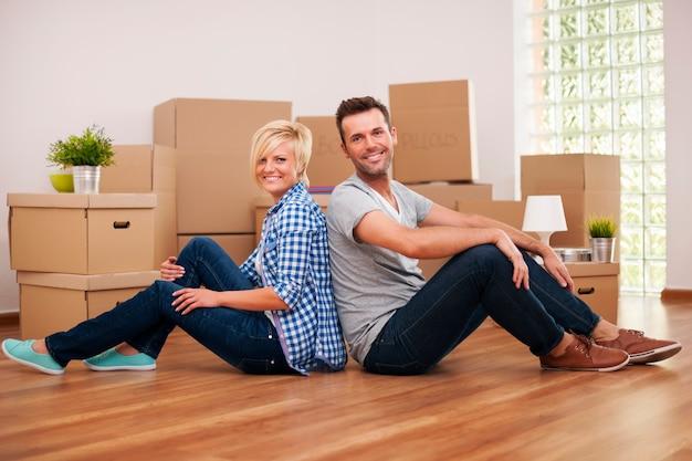Coppia felice seduti schiena contro schiena nella loro nuova casa