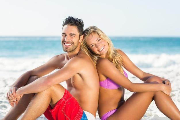 ビーチで背中合わせに座っている幸せなカップル