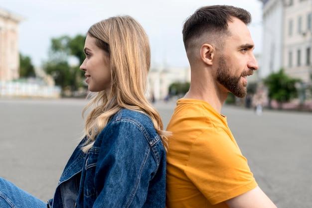 Счастливая пара, сидя спиной к спине