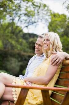 Happy couple sitting on a bench outside