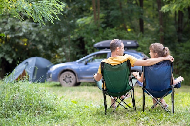 Happy couple sitting on chairs at campsite hugging together with a car and tent on background. travel and vacations concept.