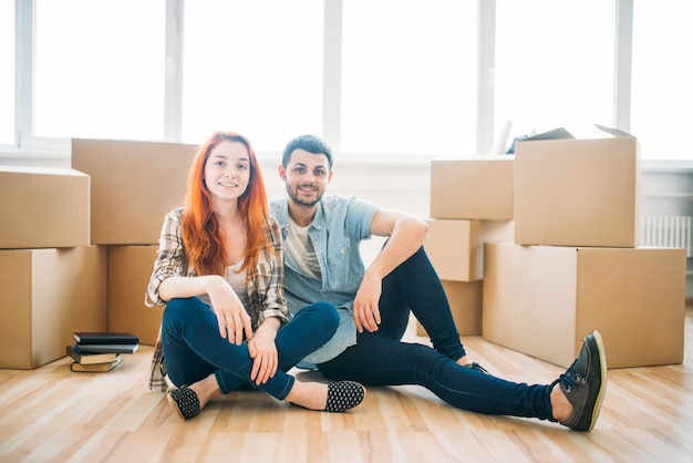 Happy couple sitting on the floor among cardboard boxes, moving to new house, housewarming
