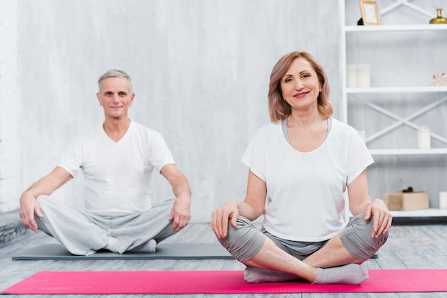 Happy couple sitting at home on yoga mat