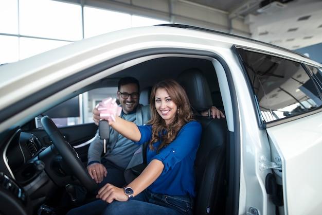 Счастливая пара сидит в новой машине, которую они только что купили, и держит ключи