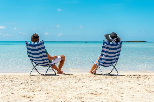 熱帯のビーチで椅子に座っている幸せなカップル