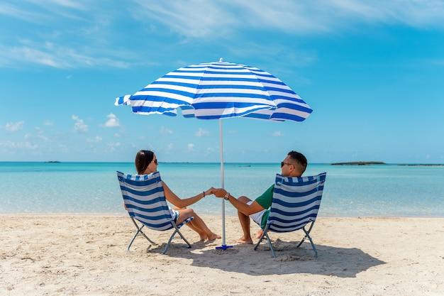 熱帯のビーチで日傘の下で椅子に座っている幸せなカップル