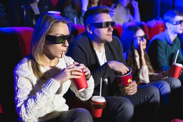 Счастливая пара, сидя в кинотеатре, смотрит 3d-фильм, ест попкорн