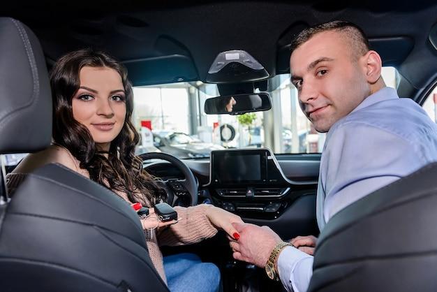 新しい車に座って、サロンで笑って幸せなカップル