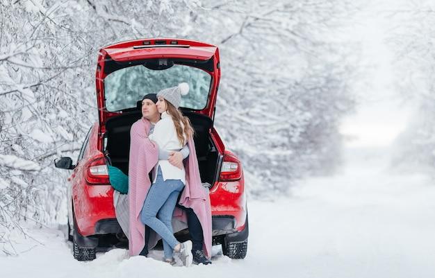 開いた車の後ろに座って、立ち寄り、コーヒーを飲みながら、幸せなカップル。ロマンチックな旅行のコンセプト。冬の森。