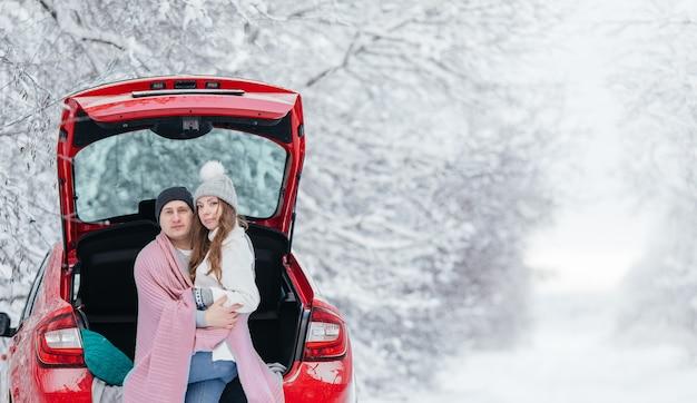 開いた車の後ろに座って、立ち寄って幸せなカップル。ロマンチックな旅行のコンセプト。冬の森。