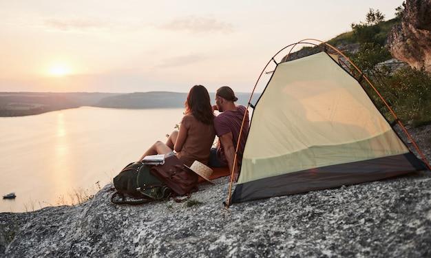 하이킹 여행 동안 호수 전망 텐트에 앉아 행복 한 커플. 모험 휴가 개념