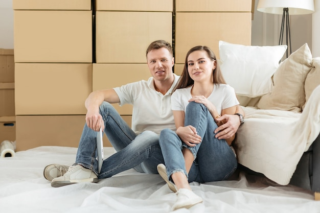 Happy couple sitting near boxes in a new apartment.
