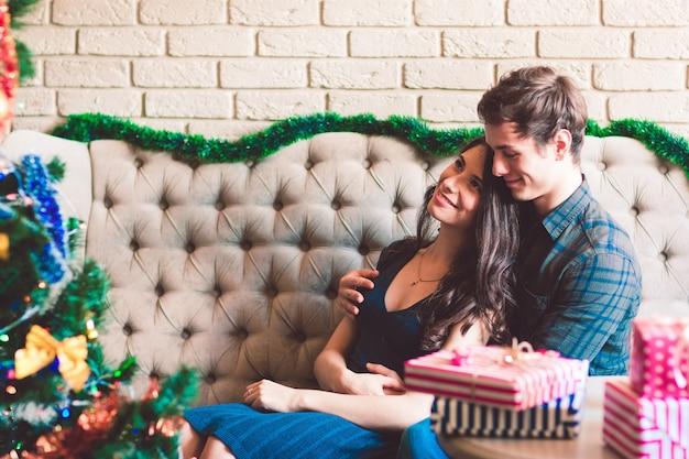 クリスマスツリーの近くに座っている幸せなカップル
