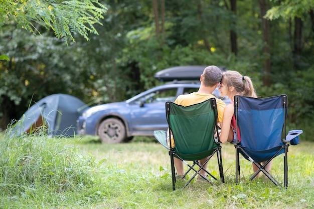 캠핑장의 의자에 앉아 서로 껴안고 있는 행복한 커플. 여행, 캠핑 및 휴가 개념입니다.