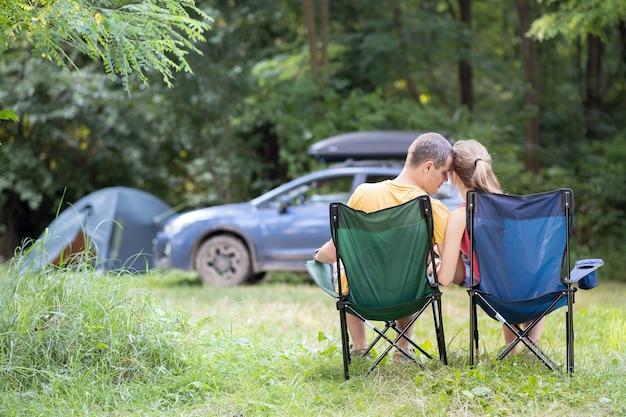 幸せなカップルが一緒にハグのキャンプ場で椅子に座っています。旅行、キャンプ、休暇の概念。