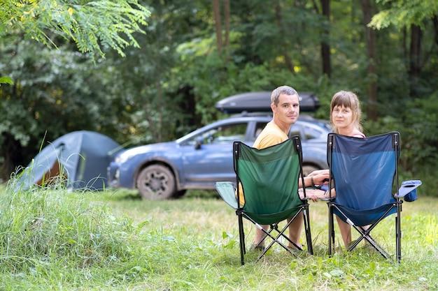 함께 편안한 캠프장에서 의자에 앉아 행복 한 커플. 여행, 캠핑 및 휴가 개념입니다.