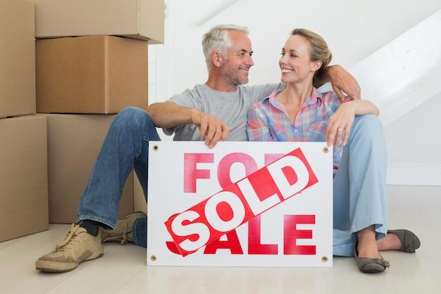 판매 기호로 바닥에 앉아 행복 한 커플