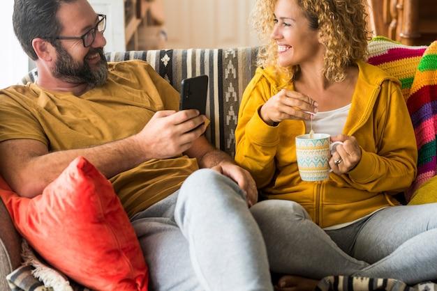 행복한 커플은 소파에 앉아 커피를 마시고 집에서 휴대전화를 사용하면서 서로를 바라보고 있습니다. 사랑하는 부부는 집에서 함께 여가 시간을 보냅니다. 마주보고 있는 커플.