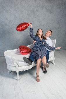 Happy couple sitting on sofa with heart balloons