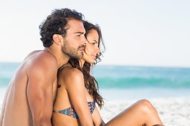 ビーチに座っている幸せなカップル