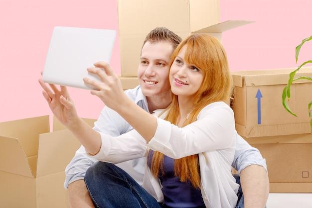 Счастливая пара сидит на полу, принимая селфи в их новом доме