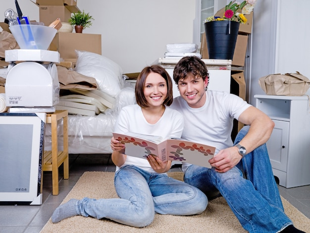 Счастливая пара, сидя на полу вместе с фотоальбомом