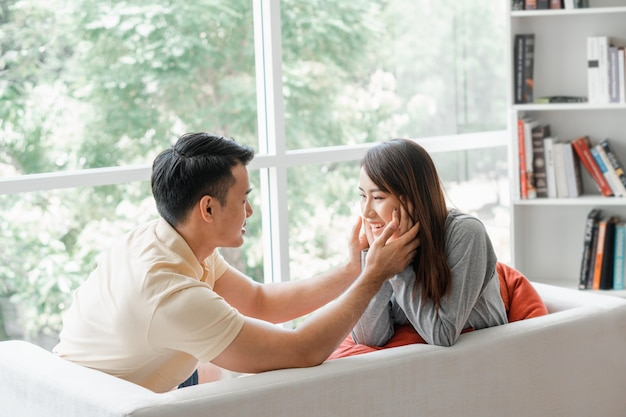 Счастливая пара, сидя на диване и будучи мужчиной, дразнит свою девушку любовью в гостиной и улыбается.