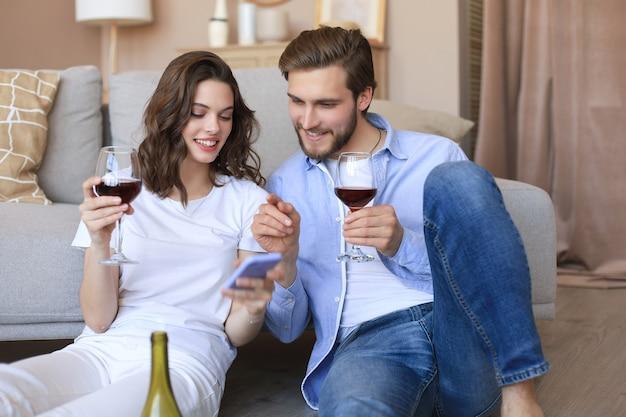 Счастливая пара сидит, отдыхает на полу в гостиной, пьет красное вино, вместе смотрит на смартфон. улыбающиеся молодые муж и жена отдыхают дома, наслаждаются романтическим свиданием на семейных выходных вместе.