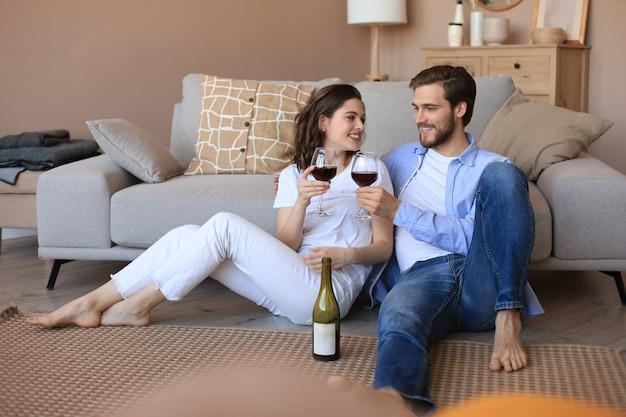 Счастливая пара сидит, расслабляясь на полу в гостиной, пьет красное вино. улыбающиеся молодые муж и жена отдыхают дома, наслаждаются романтическим свиданием на семейных выходных вместе.