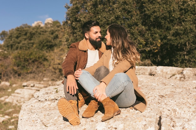 Happy couple sitting on a rock and looking at each other